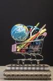 Terug naar schoolmalplaatje met veelvoudige kantoorbehoeften in karretje Stock Fotografie