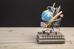 Terug naar schoolmalplaatje met veelvoudige kantoorbehoeften in karretje Stock Afbeeldingen