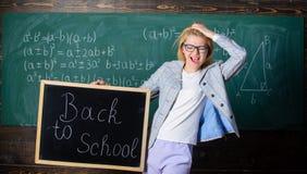 Terug naar schoolspeciale aanbieding De vrouwenleraar houdt bord terug naar schoolinschrijving op bordachtergrond apply stock afbeeldingen