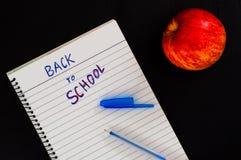 Terug naar schooltekst in gevoerde blocnote met pen en rode appel op zwarte houten achtergrond Stock Afbeeldingen