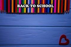 Terug naar schooltekst op heldere Kleurrijke potloden op blauwe houten lijst Royalty-vrije Stock Afbeelding