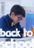 Terug naar schooltekst tegen de jongen van het bureaujonge geitje het schrijven achtergrond Stock Fotografie