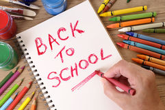 Terug naar schoolwoorden door het kleurpotlood dat van de kindholding worden geschreven Herinnering, memorandum, berichtconcept Stock Afbeeldingen