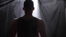 Terug van basketbalspeler het wachten in donkere nevelige ruimte en het spelen met bal stock videobeelden