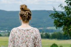 Terug van blonde bekijkt de jonge vrouw bergmening in sweater Stock Afbeeldingen