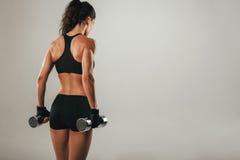Terug van de atletische gewichten van de vrouwenholding Stock Afbeelding