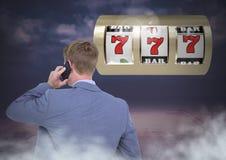 Terug van de Mens die casinogokautomaat bekijken terwijl op telefoon stock fotografie