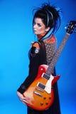 Terug van het meisje van Rotsemo het stellen met elektrische gitaar op bl Stock Foto