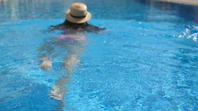 Terug van jong onherkenbaar meisje in hoed die in pool zwemmen Vrouw het ontspannen in bassin Het concept van de vakantie Achterm stock videobeelden