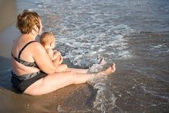 Terug van oude vrouw met baby op strand Stock Afbeeldingen