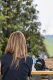 Terug van vrouw met mooie lange weggeschoten haarzitting bij buitenpicknicklijst met camera en fles water naast haar met BO Royalty-vrije Stock Afbeeldingen