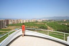 Terug van vrouw status op balkon van hotel Stock Afbeelding