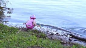 Terug van weinig leuk meisje in roze zitting op kust van rivier stock footage