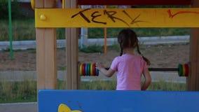 Terug van weinig mooi meisje die op houten speelplaats spelen stock video