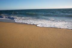 Teruggaand water op een strand Stock Fotografie