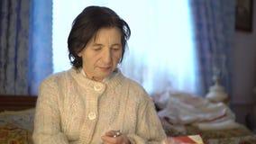 Teruggetrokken bejaarde Oekraïense vrouw die geneeskunde en het lezen gebruiken stock video