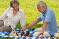 Teruggetrokken hoger paar het spelen schaak in park stock foto's