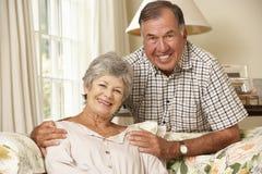 Teruggetrokken Hogere Paarzitting op Sofa At Home Together Royalty-vrije Stock Afbeeldingen