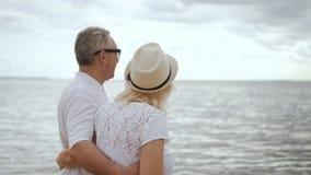 Teruggetrokken man en rijpe vrouw die aan oceaanoppervlakte samen kijken stock video