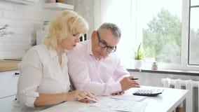 Teruggetrokken man en vrouwen het berekenen rekeningen thuis stock video