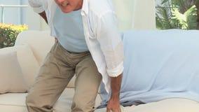 Teruggetrokken mens die een rugpijn hebben stock video