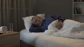 Teruggetrokken mens die nachtmerries in zijn dromen zien, die in afdeling van verpleeghuis slapen royalty-vrije stock foto's