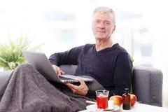 Teruggetrokken mens met laptop Stock Foto