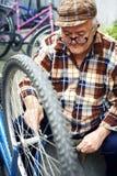 Teruggetrokken mens onderhouden fietsen royalty-vrije stock afbeeldingen