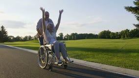 Teruggetrokken paar, vrouw die op rolstoel van het leven genieten stock video