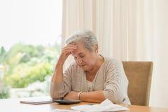 Teruggetrokken vrouw die haar binnenlandse rekeningen berekent royalty-vrije stock foto