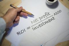 Terugkeer op investeringsverklaring op een wit blad van document tijdens een commerciële vergadering wordt gedrukt die Stock Afbeeldingen
