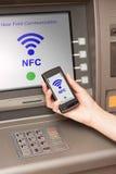 Terugtrekt geld ATM met mobiele telefoon een NFC-terminal Stock Foto's