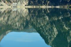 Terzaghi fördämning och reflexioner i snickaren Lake Reservoir i britt Royaltyfri Fotografi