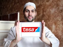 Tesa tape manufacturer logo. Logo of tesa tape manufacturer on samsung tablet holded by arab muslim man. tesa tape, inc. is a leading manufacturer of adhesive Royalty Free Stock Photography