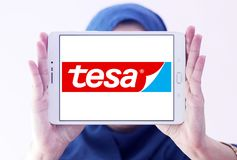 Tesa tape manufacturer logo. Logo of tesa tape manufacturer on samsung tablet holded by arab muslim woman. tesa tape, inc. is a leading manufacturer of adhesive Stock Image
