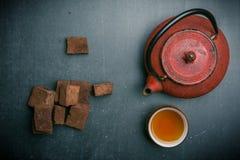 Tesammansättning med marshmallowen, tekoppen och järntekannan på mörk bakgrund royaltyfri foto