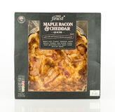Tesco finest maple bacon and cheddar quiche. WREXHAM, UK - MAY 24, 2017: Tesco finest maple bacon and cheddar quiche. Made with 100% British pork. On a white Stock Photo