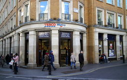 Tesco Metro Store. London, England - January 24, 2015: Pedestrians pass by the Tesco Metro store near Covent Garden in London, England. Tesco was founded in 1919 Royalty Free Stock Photos