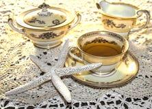 Teservis med guldklippning och designer Royaltyfri Foto