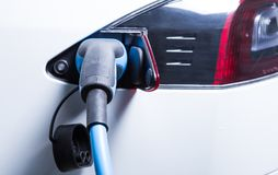 Tesla car charging with electric cord plugged in. Near back stop lights Stock Photo