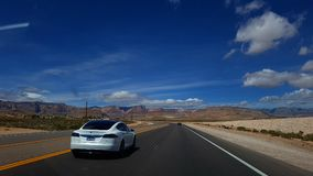 Tesla car in Death Valley. A white Tesla car driving along a road in Death Valley, California stock images