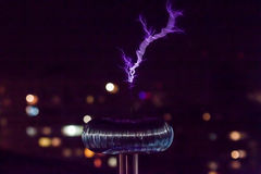 Tesla coil with blue lightning. On city lights background Royalty Free Stock Photos