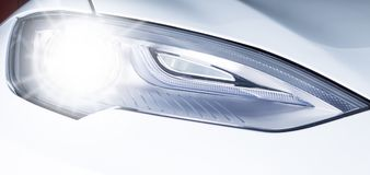 Tesla headlight on. Closeup picture of shiny Elon Musk electric car solutions Stock Images