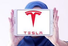 Tesla logo. Logo of tesla company on samsung tablet holded by arab muslim woman. tesla is an American automaker, energy storage company, and solar panel Royalty Free Stock Photography