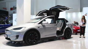 Tesla Model X all-electric, luxury, crossover SUV car with opening doors. And a woman standing next to the car during the 2017 European Motor Show Brussels stock footage