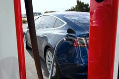Tesla model 3 new electric car. Seaside, CA - January 6, 2018: newest navy tesla model 3 charging at supercharger station Stock Images