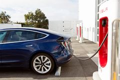 Tesla model 3 new electric car. Seaside, CA - January 6, 2018: newest navy tesla model 3 charging at supercharger station Stock Image