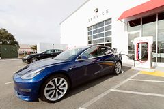 Tesla model 3 new electric car. Seaside, CA - January 6, 2018: newest navy tesla model 3 charging at supercharger station Royalty Free Stock Photography