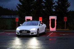 Tesla Model S Arrives at Supercharger Station at Night royalty free stock images