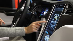 Tesla Model X electric car. Woman tasting a new vehicle functions.